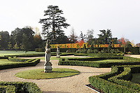 A classical statue gazes across the grounds towards a pair of gardeners working on some box hedges