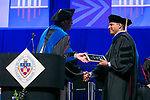 """Sanjay Deshmukh, right, receives the Constantine """"Gus"""" Economies Distinguished Teaching Award from Ray Whittington, dean of the Driehaus College of Business, Sunday, June 11, 2017, during the DePaul University Driehaus College of Business commencement ceremony at the Allstate Arena in Rosemont, IL. (DePaul University/Jamie Moncrief)"""