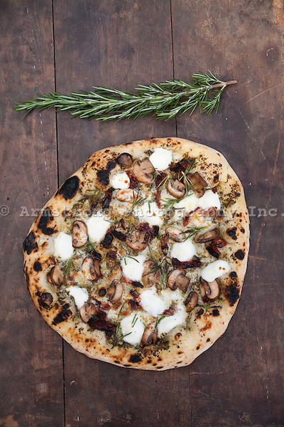 Overhead view of a fresh baked pizza with blistered crust, topped with mushrooms, pesto, fresh mozzarella, and rosemary. On a wooden surface with a sprig of fresh rosemary.