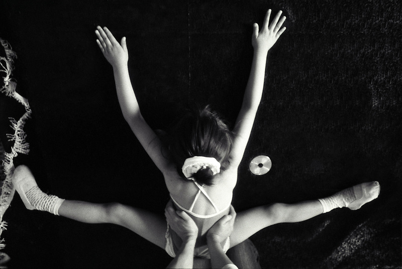 A young contortionist streches before a class.