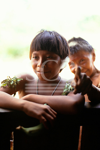 Roraima, Brazil. Yanomami woman with leaf amulet decorations and feather ear plug and her husband.