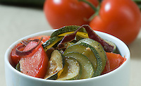 Zucchini squash  and tomato skillet meal in white bowl studio