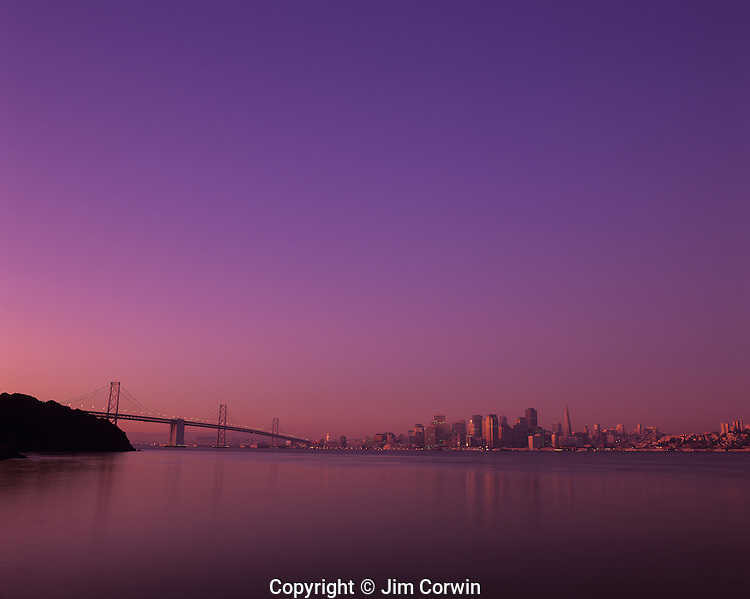 San Francisco skyline at sunrise with city buildings reflected in serene, calm bay from Treasure Island, San Francisco, California USA