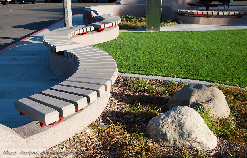 "Curved, slatted, anti-skateboarding benches form one edge of Circle Park, a pocket park located on Park Circle Drive in Anaheim, California.  Artificial turf makes up the ""lawn"" in the park, along with some drought-resistant landscaping."