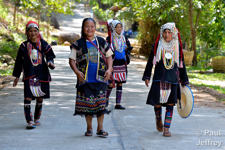 Traditionally dressed women walk along a road in Buyer, a small village in northern Thailand populated by indigenous hill tribe people.