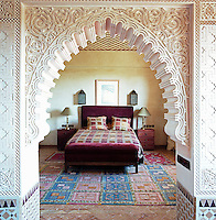 A view through an ornate plasterwork arch to a bedroom furnished with a bed upholstered in burgundy velvet
