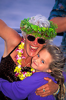 Jubilant older woman celebrating her birthday wearing a haku and plumeria lei is embraced by young girl.