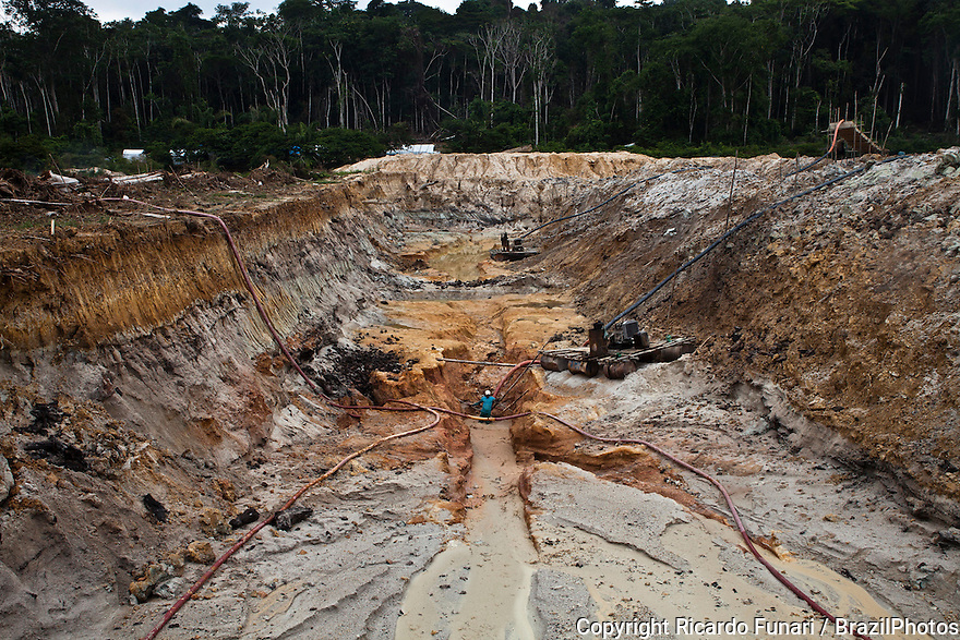 """Gold mining, Amazon deforestation - hydraulic mining known as """"chupadeira system"""", a form of mining that uses high-pressure jets of water to dislodge rock material or move sediment.  Workers clear the designated work front and then dug down to the level of ore-bearing material. Large and deep holes are made in forest land. Amazon rain forest deforestation, Agua Branca gold mining village, Para State, Brazil."""