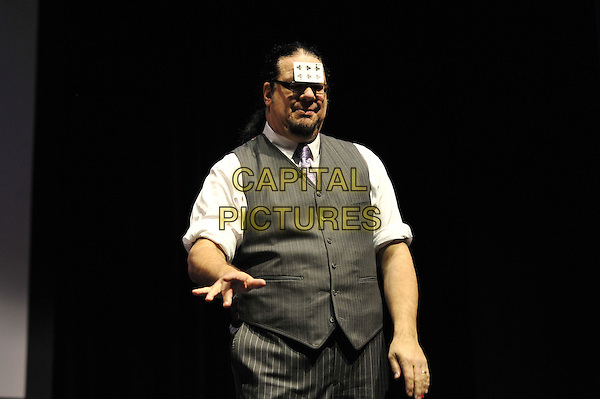 Penn Jillette .Penn and Teller performing 'Conversations with Penn and Teller - 35 Years of Magic and Bulls'%+t', indigo2, Greenwich, London, England. .7th December 2011.bullshit stage concert performing performance half length grey gray waistcoat white shirt pinstripe card on forehead .CAP/MAR.© Martin Harris/Capital Pictures.