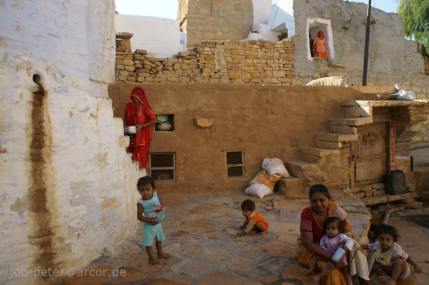 street scene with woman in red sari and children in Fort Jaisalmer, Rajastan, India. The architecture in the background is part of the walls of Fort Jaisalmer.