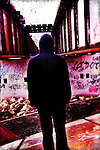 rear view of a hooded man in front of a wall of graffiti.