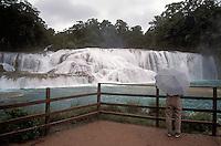 Woman with unbrella admiring the Agua Azul waterfalls in Chiapas, Mexico