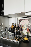 Bottles and a decanter arranged on a tray on the kitchen worktop reflect the black and white monochrome theme used throughout the apartment.