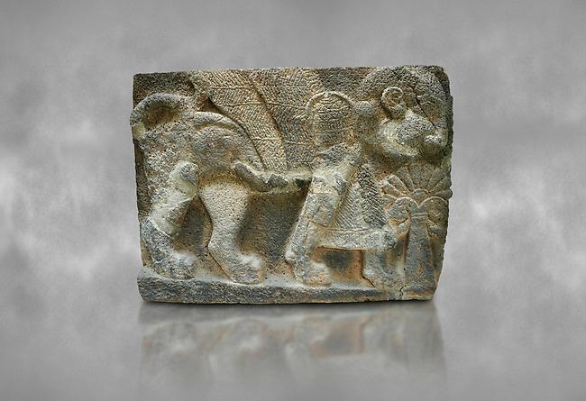 Pictures & images of the North Gate Hittite sculpture stele depicting Hittite winged God. 8th century BC. Karatepe Aslantas Open-Air Museum (Karatepe-Aslantaş Açık Hava Müzesi), Osmaniye Province, Turkey. Against grey art background