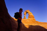 Hiker with a day pack beneath Delicate Arch in Arches National Monument, Utah The Worlds most famous natural bridge in yellow sandstone
