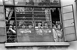 Blair Peach funeral.  Southall west London 1979. Factory workers crowd the windows of their work place to watch the funeral cortege.