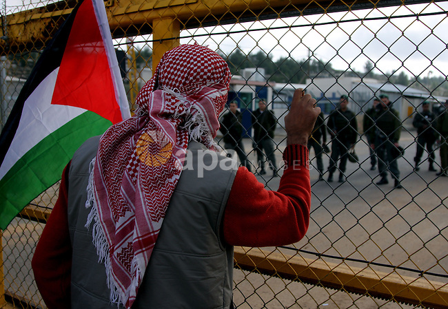 A Palestinian holds a flag outside Ofer prison near the West Bank city of Ramallah December 29, 2009, during a protest calling for the release of Palestinian prisoners from Israeli jails. Photo by Issam Rimawi