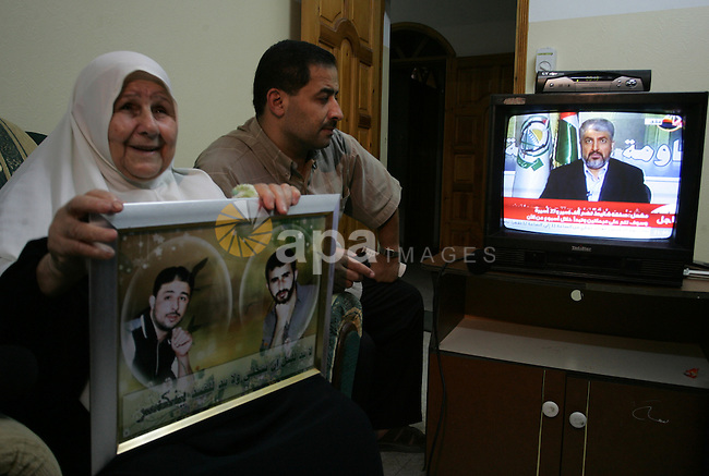 The Family of Hassan Salame, watch a television broadcasting the speech of Hamas leader Khaled Meshaal, celebrating a deal that will see Palestinian detainees freed in exchange for Israeli soldier Gilad Shalit, Hassan Salame a Hamas leader imprisoned for life for attacks committed in Israel, holds a portrait of their son at their house in Khan Yunis, southern Gaza Strip on October 11, 2011. Salama is one of the founders of Hamas? armed wing, the Ezzedine al-Qassan Brigades and is the mastermind of several deadly attacks committed in Israel.. Photo by Abed Rahim Khatib