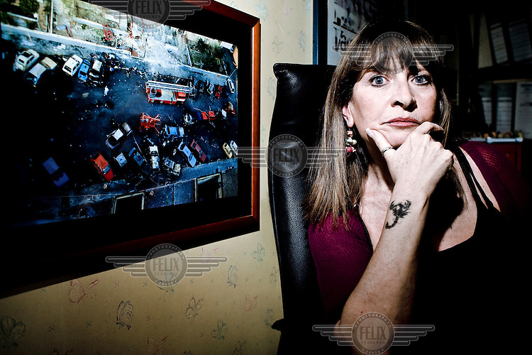 Lawyer Rosalba Di Gregorio in her office beside a picture of the Via D'Amelio massacre, where the judge Paolo Borsellino was killed. Rosalba Di Gregorio is one of Palermo's most notorious criminal lawyers. Since acting on behalf of defendants in the groundbreaking Maxi Processo ('Supergrass') trial in the mid 1980s, Di Gregorio has defended dozens of members of the Sicilian Mafia, or Cosa Nostra, including Vittorio Mangano; Palermo boss, Pietro Aglieri; and the boss of bosses, Bernardo Provenzano, who was sentenced to life for the massacres at Capaci and Via D'Amelio..