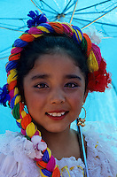 Portrait of a small girl in traditional costume under an umbrella at a Santa Fe festival with folkdance in  New Mexico, USA