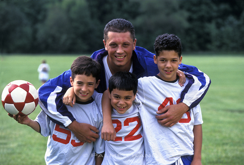 Latino Soccer coach poses with players