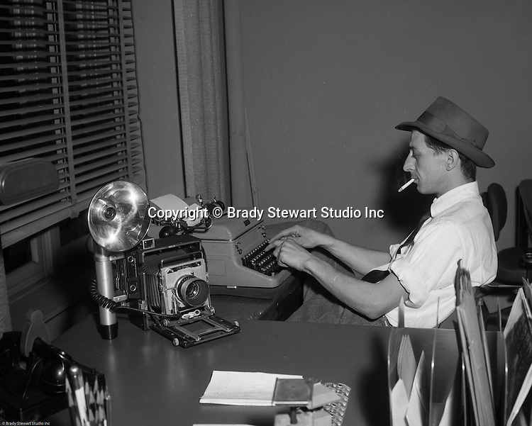 Pittsburgh PA:  Ross Catanza filling out paperwork after completing another successful day on location for Brady Stewart Studio - 1956.  Ross worked for Brady Stewart Studio from 1950 to 1965 when he left to pursue an award winning career at the Pittsburgh Post Gazette newspaper.
