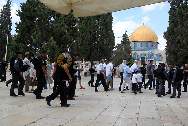 Israeli Jewish settlers walk with Israeli police in front of the Dome of the Rock mosque in Jerusalem's old city on September 30, 2015. Photo by Mahfouz Abu Turk