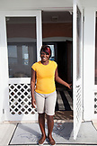 EXUMAS, Bahamas. A staff person in front of a door of the Hill House at Fowl Cay Resort.
