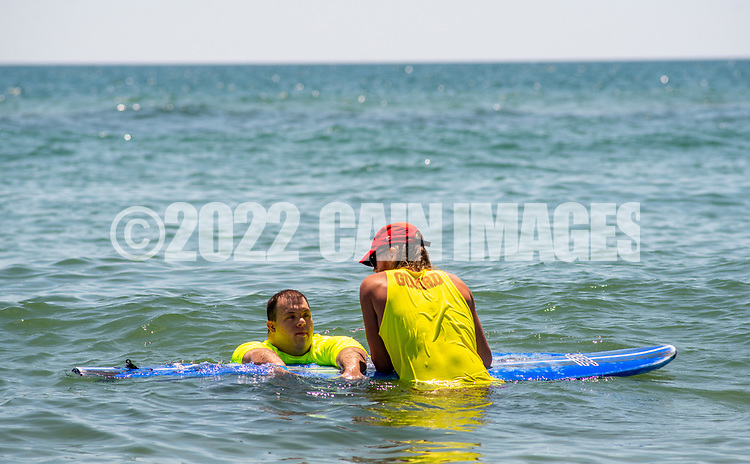Lifeguard John Livingstone, 24 of Medford, New Jersey helps guide Anthony Tarquinio, 27, of Beuna, New Jersey chat while resting on a paddle board during the 11th annual 21 Down Beach Day Monday, July 15, 2019 at Schellenger Street beach in Wildwood, New Jersey. Every summer, the Wildwood Beach Patrol opens Lincoln Ave Beach for kids with down syndrome and their families for 21 Down Beach Day. Often, kids with down syndrome aren't comfortable in the ocean. Their parents can't just relax and watch them frolic. But on July 15th, the kids swim with seasoned Wildwood lifeguards on soft-top paddle boards. (Photo by William Thomas Cain / CAIN IMAGES)