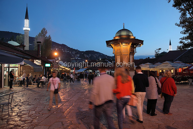 The Sebilj at night, a public fountain in Ottoman style made from wood on a stone base, built 1891, in Bascarsija Square, Sarajevo, Bosnia and Herzegovina. Behind is the 16th century Gazi Husrev-beg Mosque. The square is also called Pigeon Square as people sit in the cafes drinking coffee and feeding the many pigeons which congregate here. The city was founded by the Ottomans in 1461. Picture by Manuel Cohen