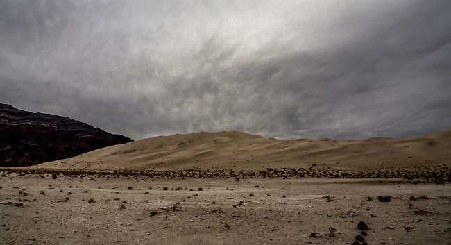 The sun struggles to appear through the clouds at Eureka Dunes at Death Valley National Park, California