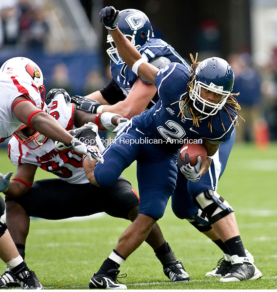 EAST HARTFORD, CT - 17 OCTOBER 2009 -101709JT05-<br /> UConn's Andre Dixon runs away from Louisville's Malcolm Tatum (90) as Dixon's teammate Mike Ryan (71) covers him in the background and Louisville's Antwon Canady, left, eventually tackles Dixon during Saturday's game at Rentschler Field.<br /> Josalee Thrift Republican-American