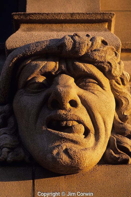 """Gargoyle on side of building at sunset, grotesque expression, along the """"AVE"""" University District, Seattle, Washington State USA"""