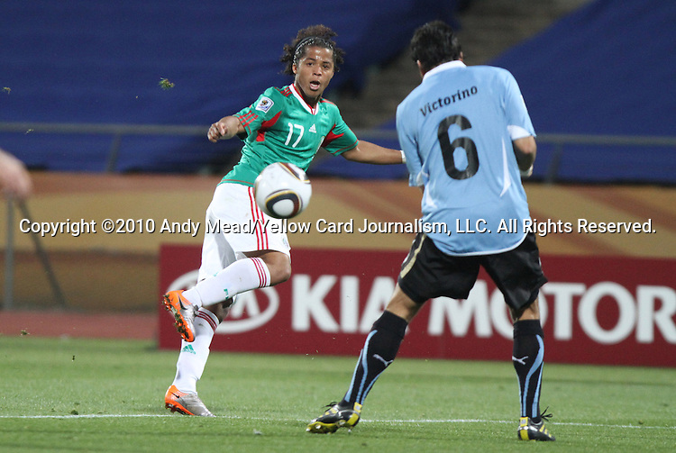 22 JUN 2010: Giovani Dos Santos (MEX) (17) sends the ball past Mauricio Victorino (URU) (6). The Mexico National Team lost 1-2 to the Uruguay National Team at Royal Bafokeng Stadium in Rustenburg, South Africa in a 2010 FIFA World Cup Group A match.