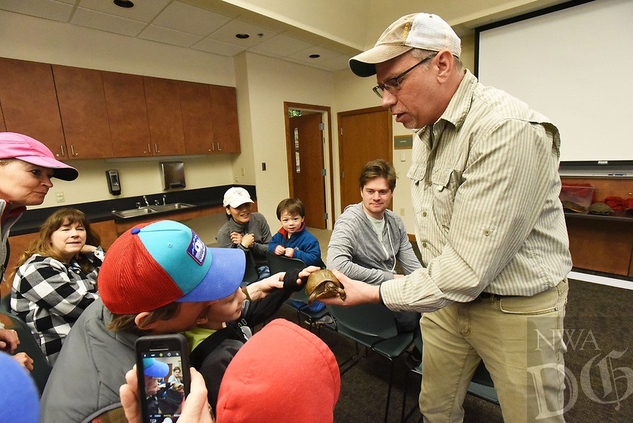 NWA Democrat-Gazette/FLIP PUTTHOFF <br /> OUT OF ITS SHELL<br /> Chris Pistole, interpreter at Hobbs State Park-Conservation Area, lets visitors on Saturday March 23 2019 feel the shell of a box turtle during his program on reptiles at the park. Pistole also brought a speckled king snake for visitors to touch.