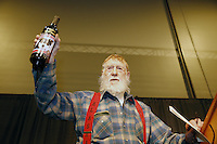 Thursday February 28, 2013  Dick Newton, widower of the late Jan Newton, holds a bottle of wine with his wife's photo on it as the honorary musher of the 2013 race at the musher drawing banquet held at the Dena'ina Convention Center in Anchorage two days prior to the start of Iditarod 2013...Photo (C) Jeff Schultz/IditarodPhotos.com  Do not reproduce without permission.