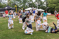 Children compete in a potato sack race at a fair in Washington Heights in New York on Saturday, July 25, 2015. (© Richard B. Levine)