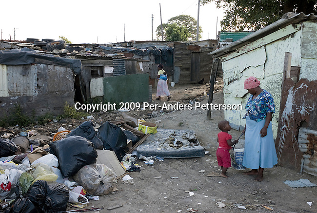 EAST LONDON, SOUTH AFRICA - MARCH 9:  A mother stands with her son outside their shack on March 9, 2009, in Duncan Village a poor township outside East London, South Africa. This area is one of the most popular ANC areas and many of its leaders grew up in the Eastern Cape province. Many people are disappointed in the ruling party and after 15 years of power, people?s lives have not changed much to the better. In Duncan Village, there?s lack of service delivery such as housing, electricity, and running water. Garbage is left on the streets and the municipality is only collecting it once a week, or they often skip a week. About 23 million South Africans are registered to vote on the April 22 national election. Jacob Zuma will most likely be the third elected head of a democratic South Africa. (Photo by: Per-Anders Pettersson/Getty Images)...