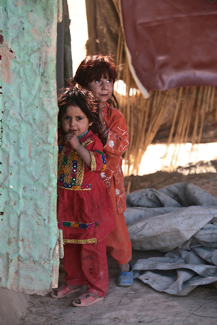 Two girls watch U.S. Marines from Company I, 3rd Battalion, 4th Marine Regiment, as they patrol the town of Delaram, in western Afghainstan's Farah province. Nov. 8, 2009. DREW BROWN/STARS AND STRIPES