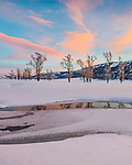 Yellowstone National Park, Wyoming: Colorful clouds and cottonwoods reflected in the Lamar River at sunset in the Lamar Valley with Amethyst Peak in the distance