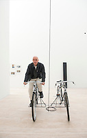 Patrick Charpenel director for the new Jumex Museum riding a bicycle, part of an instalation by artist Mauritzio Cattelan.  Mexico City