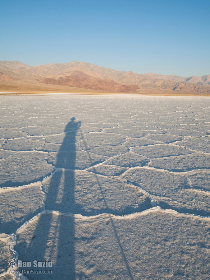 Photographer's shadow on salt pan at sunrise, Death Valley National Park, California
