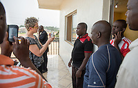 Occidental College professor Mary Beth Heffernan works with ambulance crews at the National Mandingo Caucus of Liberia in Jacob Town, Monrovia, Liberia on Tuesday, March 3, 2015. Professor Heffernan's PPE Portrait Project involves creating wearable portraits of health care workers who must wear PPE, or personal protective equipment. The National Mandingo Caucus of Liberia is an ambulance service that removes dead bodies, in addition to people injured and sick, so crews must wear PPE to help stop the spread of Ebola and other diseases. Ambulance companies, such as this one, must gain the trust of the community in which they are based and hope that placing their images on their PPEs will help. <br /> (Photo by Marc Campos, Occidental College Photographer) Mary Beth Heffernan, professor of art and art history at Occidental College, works in Monrovia the capital of Liberia, Africa in 2015. Professor Heffernan was there to work on her PPE (personal protective equipment) Portrait Project, which helps health care workers and patients fighting the Ebola virus disease in West Africa.<br />