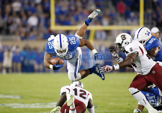 Kentucky Wildcats running back Jonathan George (25) jumps over a South Carolina player at the University of Kentucky football vs.  South Carolina at Commonwealth Stadium in Lexington, Ky., on Saturday, September 29, 2012. Photo by Tessa Lighty | Staff