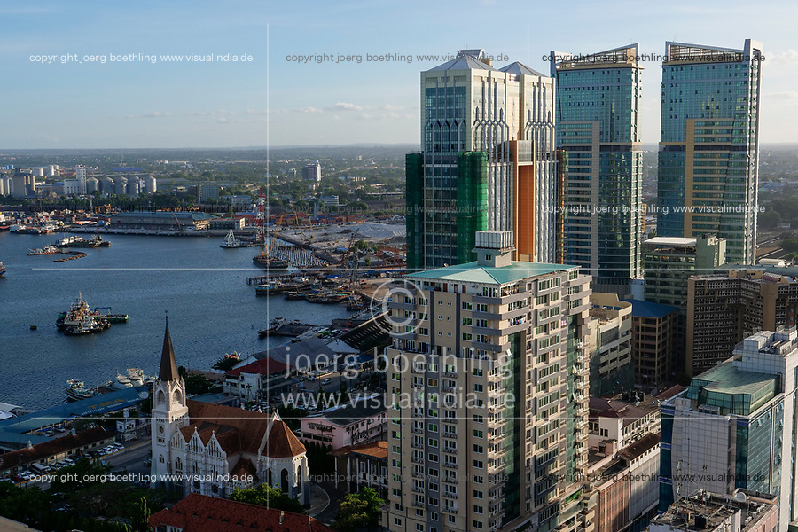 TANZANIA Daressalaam, bay and seaport, in front new apartment tower and catholic St. Joseph cathedral, built during german colonial time