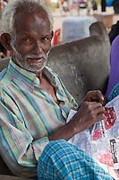 Myanmar, Burma, Yangon.  Old Man Reading Newspaper.