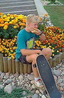 Skateboarder age 15 eating fast food hamburger by flowers.  South Dakota USA