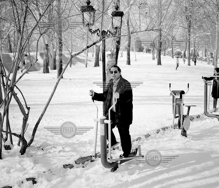A man uses public exercise machines in a snow covered city park.