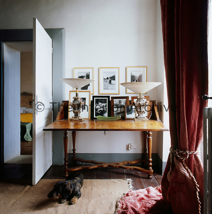 Two lamps with inverted shades are displayed on an antique table along with several black and white photographs in frames. A dog lies on a rug nearby. A red curtain is tied back at the window.
