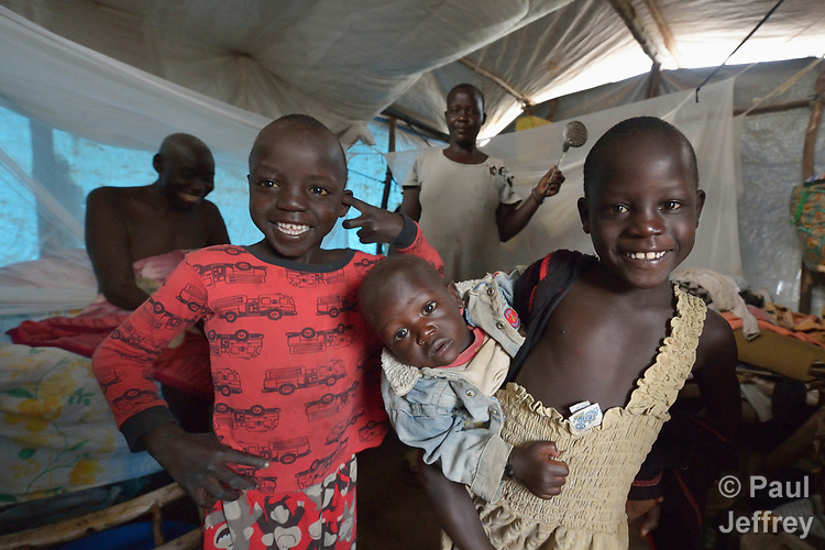 Nema Chandiru, in the background, and some of her children pose in their shelter in the Rhino Refugee Camp in northern Uganda. As of April 2017, the camp held almost 87,000 refugees from South Sudan, and more people were arriving daily. About 1.8 million people have fled South Sudan since civil war broke out there at the end of 2013. About 900,000 have sought refuge in Uganda. <br /> <br /> Chandiru's family came to Rhino from Morobo, South Sudan, in 2016.